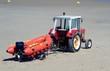 roter Traktor mit Motorschlauchboot auf einem Trailer am Sandstrand