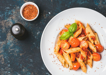 Pasta penne with tomato sauce, basil and roasted tomatoes. Old painted dark plywood background, top view, copy space, horizontal composition