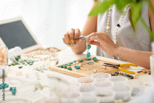 Hands of woman using pliers when assembling earring Canvas Print