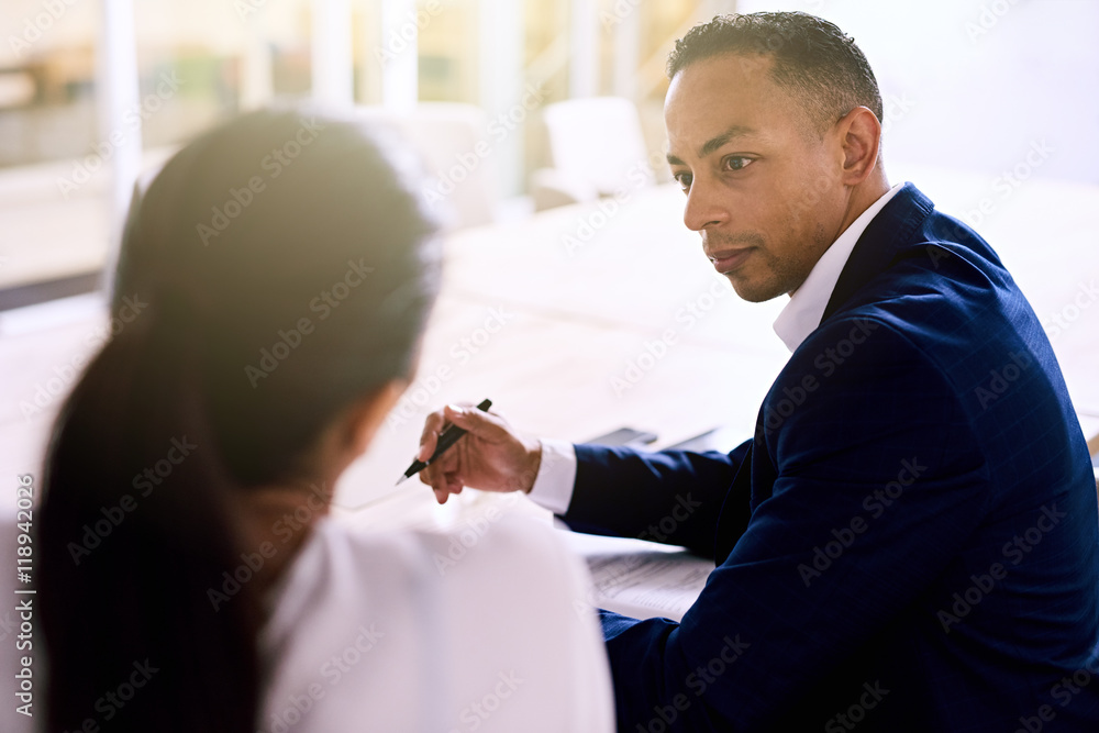 Fototapety, obrazy: Over the shoulder shot of handsome businessman busy talking to his female colleague during their scheduled business meeting, both well dressed individuals of mixed ethnic complexion.