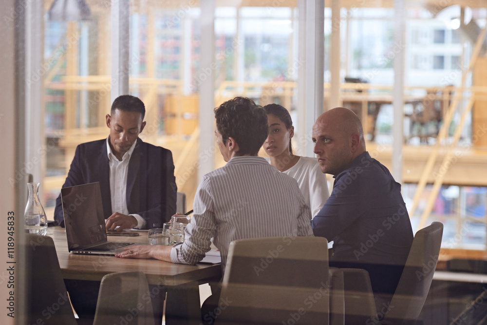 Fototapety, obrazy: Group of four dynamic business executives sitting toether in a meeting about their company's future in the firms newly renovated conference room.
