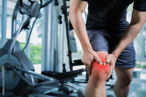 Fotografia  Healthy men Injury from exercise in the gym, he injured his knee