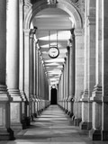 Long colonnafe corridor with columns and clock hanging from ceiling. Cloister perspective. . Black and white image. - 118953427