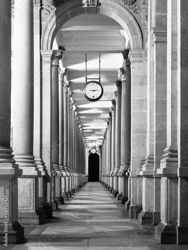 dlugi-korytarz-z-kolumnami-i-zegarem-zwisajacym-z-sufitu