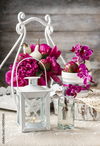 Photo  White lantern and floral arrangement with pink peonies and viole