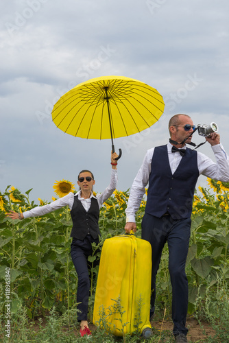Man and woman in suits made their way among sunflowers and something photographe плакат