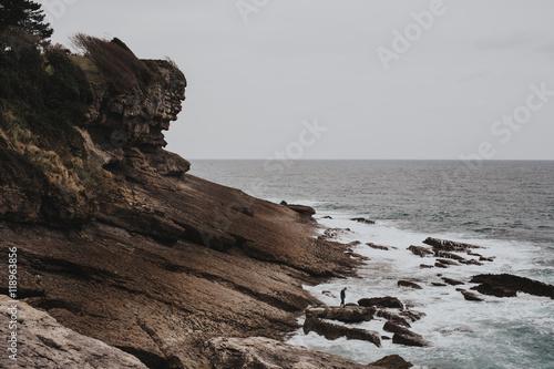 Unrecognizable person on rocks at coastline