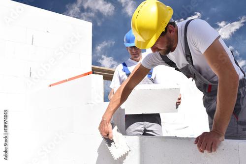 Fotografía  Bauarbeiter auf einer Baustelle - Maurer beim Rohbau // construction workers