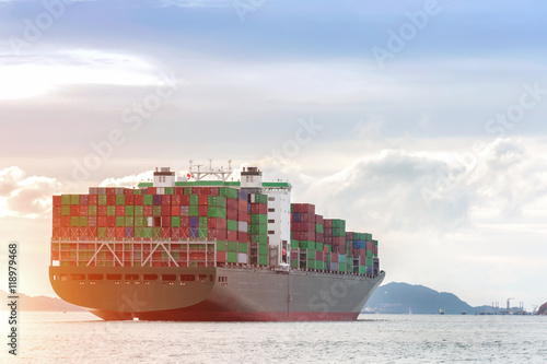 Container Cargo freight ship with working crane bridge in shipyard at dusk for Logistic Import Export background sunrise,sun light.