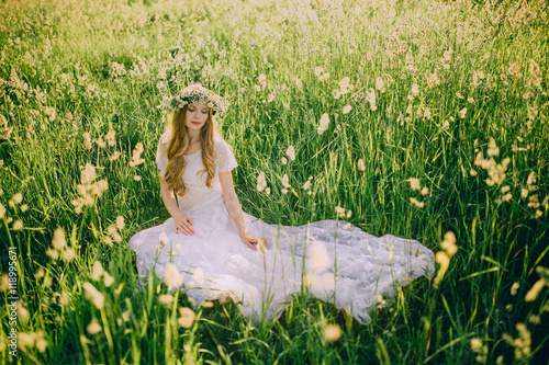 Photo  Young girl in a white dress in the meadow