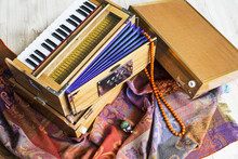 Indian Harmonium, A Traditional Wooden Keyboard Instrument, Close-up.  Bright Colorful Musical Instrument On The Patterned Wrap