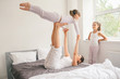 Mother with children doing yoga exercise in bed