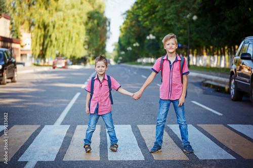Photo  Kids with backpack walking, holding on warm day  on the road .