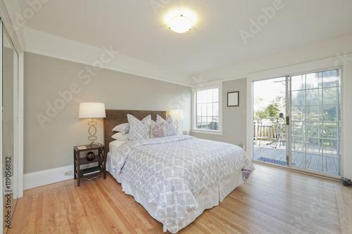 Bedroom With Wooden Floor And Sliding Glass Door Leading To Balc