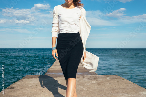 Fotomural  Elegant woman in a skirt and cardigan walks on the background of