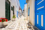 Fototapeta Uliczki - Typical white Greek houses with blue doors and windows on street of beautiful Mykonos town, Cyclades islands, Greece