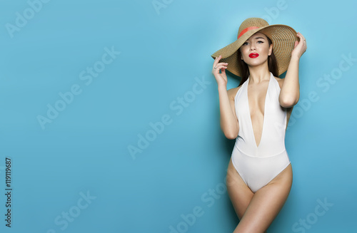 Photo  sexy girl in panama in white bikini on a blue background stands sideways and hat