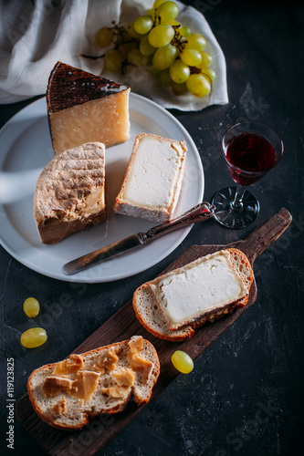 Closeup of cheese on plate and a red wine