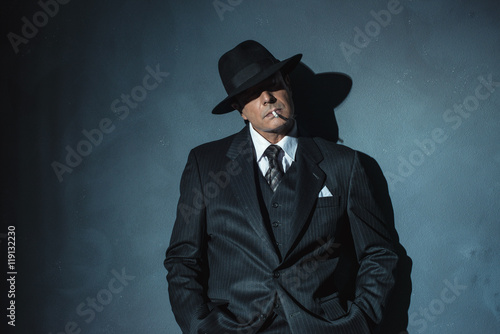 Fotografie, Tablou  Retro 1940 film noir gangster wearing suit and hat. Smoking ciga