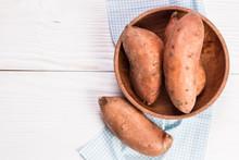 Raw Sweet Potatoes On Wooden B...