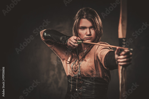 Serious viking woman with bow and arrow in a traditional warrior clothes, posing on a dark background Fototapeta