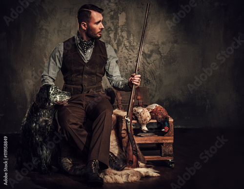 Fotografering Handsome hunter with a english setter and shotgun in a traditional shooting clothing, sitting on a dark background