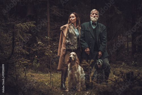 Two hunters with dogs and shotguns in a traditional shooting clothing, posing on a dark forest background Canvas Print