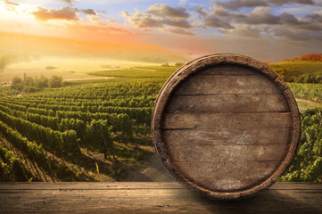 FototapetaRed wine with barrel on vineyard in green Tuscany, Italy