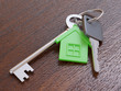 Green house keychain and keys on table close-up