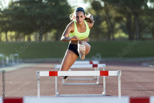 Fotografía  Young athlete jumping over a hurdle during training on race trac