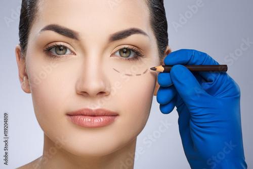 Obraz Surgeon drawing dashed line under eye - fototapety do salonu