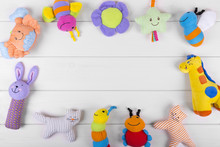 Colorful Soft Baby Toys On Wooden Background With Copy Space
