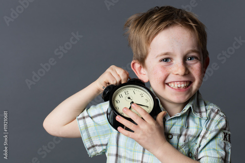 happy young kid with missing tooth enjoying holding alarm