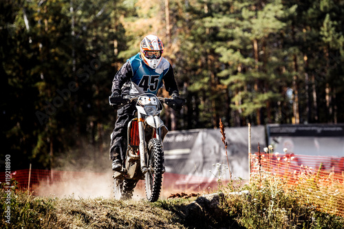 Photo male rider on a motorcycle when racing Enduro, dust from under rear wheels