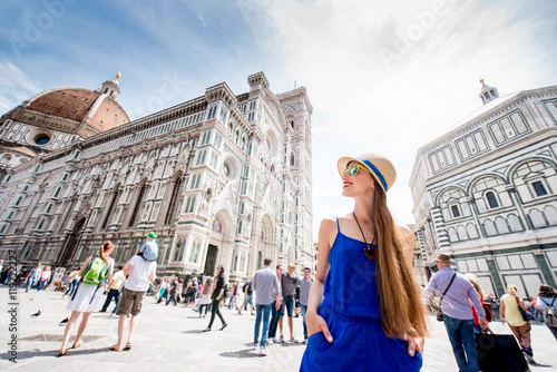 Fotografia Young female traveler standing on Cathedral square in front of Santa Maria del Fiore church in Florence