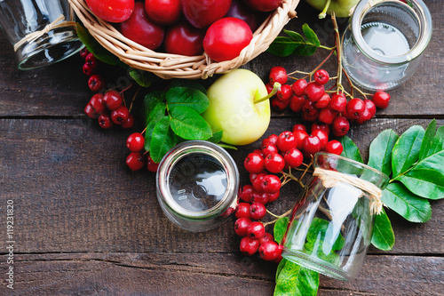 Fotografie, Obraz  Plums in a basket, apples, rowanberry and glass jars