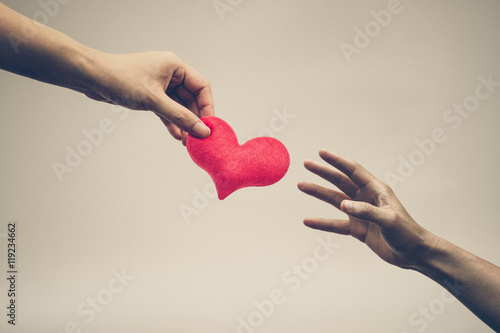 female hand giving a red heart to a male hand Tapéta, Fotótapéta