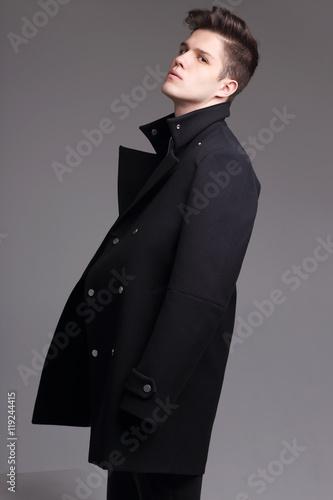 Fotografie, Tablou  Fashion shot of a young handsome man in black coat.
