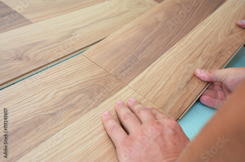Fotografia, Obraz  Installing laminate flooring fitting the next piece