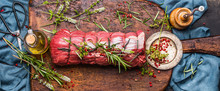 Raw Roast Beef  With Herbs Tied With A Rope With Cooking Ingredients, Oil  And Spices On Rustic Background, Top View, Banner