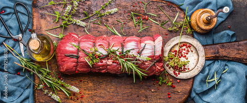 Fotografie, Obraz  Raw roast beef  with herbs tied with a rope with cooking ingredients, oil  and s