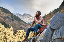 Contemplative Bearded Man With Luggage On Top Of Mountain Relaxing