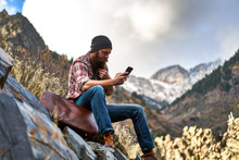 Hipster Vagabond Using Smart Phone Out In The Mountains