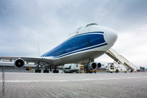 Foto op Aluminium Luchthaven Cargo wide-body plane and aircraft passenger loader near terminal