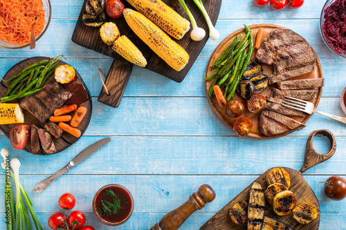Aluminium Prints Grill / Barbecue Grilled beef steak with grilled vegetables on wooden blue table