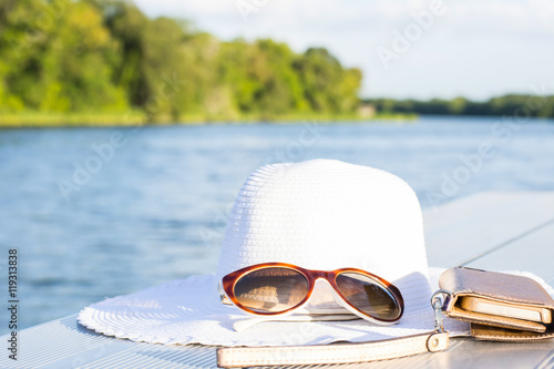 Fotomural vacation and technology accessories on lakeside smartphone,  hat