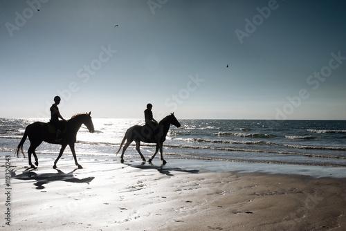 Poster de jardin Equitation 2 cavalièrese le soir sur la plage