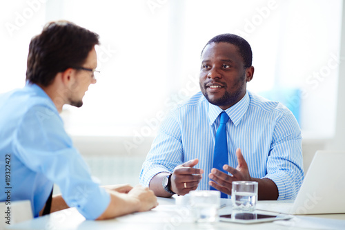 Fototapety, obrazy: Shot of African-American businessman in shirt and necktie discussing work with Caucasian colleague in shirt and glasses in office.