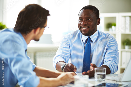 Smiling African-American businessman in shirt and necktie sitting in office talk Canvas Print
