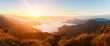 Panorama of beautiful sunrise in the mountains with white fog between peaks. Banner. Selective focus.